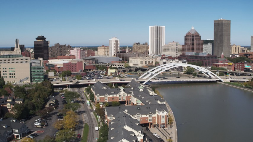 5.7K stock footage aerial video of the skyline behind bridge over Genesee River, Downtown Rochester, New York Aerial Stock Footage | DX0002_207_011