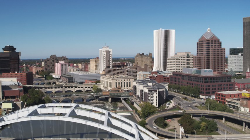 5.7K stock footage aerial video flyby bridges spanning Genesee River with view of The Metropolitan skyscraper, Downtown Rochester, New York Aerial Stock Footage | DX0002_207_028