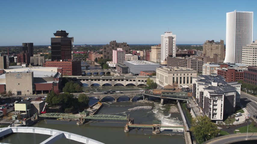 5.7K stock footage aerial video of passing bridges over the river and city buildings, Downtown Rochester, New York Aerial Stock Footage | DX0002_207_033