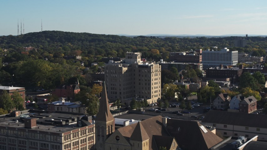 5.7K stock footage aerial video flying away from office building, reveal church in Rochester, New York Aerial Stock Footage | DX0002_208_029