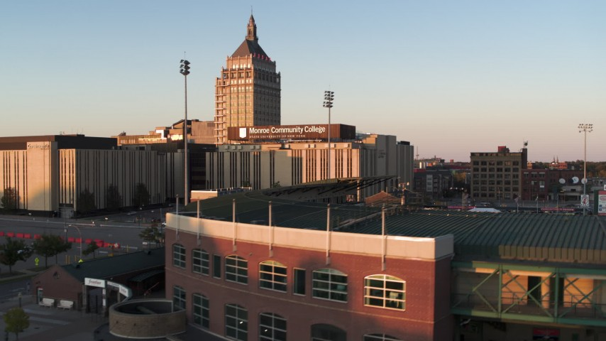 5.7K stock footage aerial video fly over Frontier Field toward college and Kodak Tower at sunset, Rochester, New York Aerial Stock Footage | DX0002_209_035