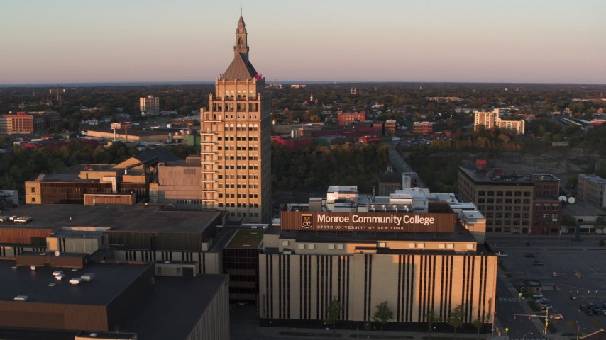 5.7K stock footage aerial video of a reverse view of a college and Kodak Tower at sunset, Rochester, New York Aerial Stock Footage | DX0002_209_038