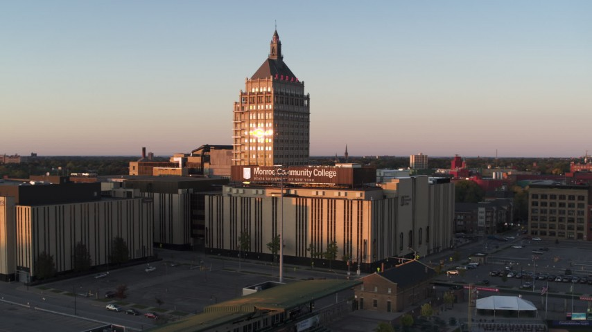 5.7K stock footage aerial video descend away from Kodak Tower and a college at sunset, Rochester, New York Aerial Stock Footage | DX0002_209_040