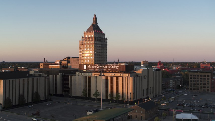 5.7K stock footage aerial video ascending toward Kodak Tower and a college at sunset, Rochester, New York Aerial Stock Footage | DX0002_209_041
