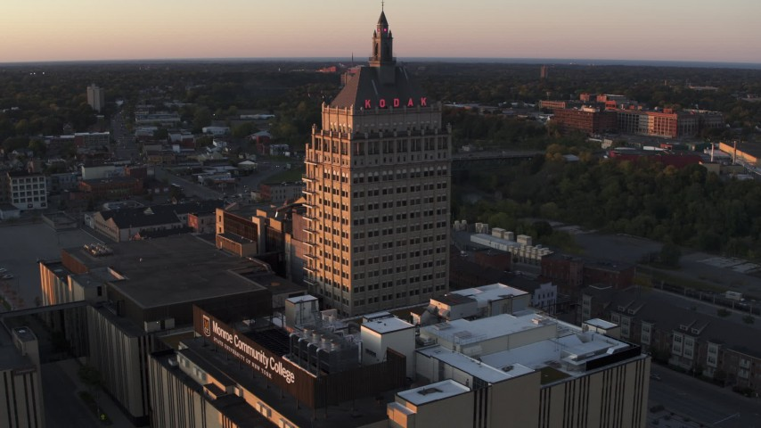 5.7K stock footage aerial video stationary view of Kodak Tower and a college at sunset, Rochester, New York Aerial Stock Footage | DX0002_209_042