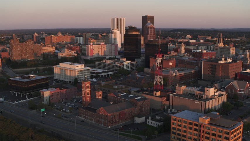 5.7K stock footage aerial video focus on First Federal Plaza while passing a radio tower at sunset, Downtown Rochester, New York Aerial Stock Footage | DX0002_209_043