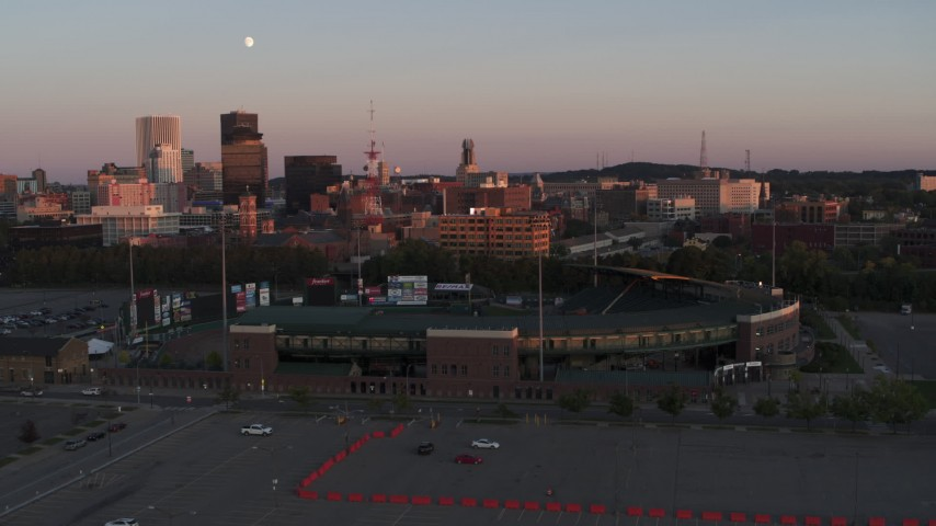 5.7K stock footage aerial video fly away from office buildings and radio tower at sunset, reveal stadium, Downtown Rochester, New York Aerial Stock Footage | DX0002_209_046