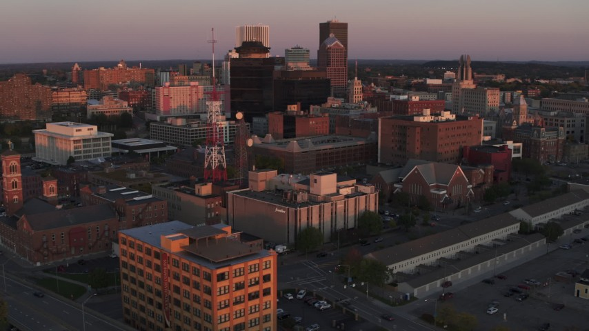 5.7K stock footage aerial video of orbiting a radio tower and office buildings at sunset, Downtown Rochester, New York Aerial Stock Footage | DX0002_209_049