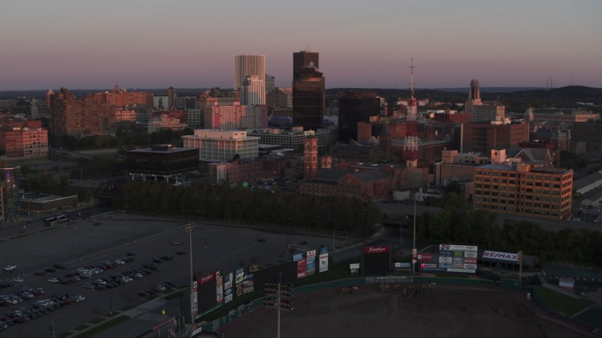 5.7K stock footage aerial video reverse view of a radio tower and office buildings at sunset, Downtown Rochester, New York Aerial Stock Footage | DX0002_209_051