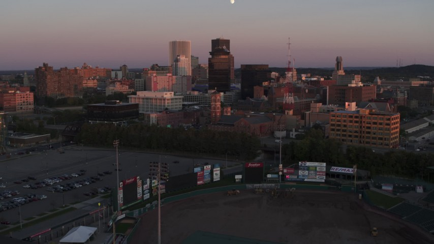 5.7K stock footage aerial video of flying by a radio tower and office buildings at sunset, Downtown Rochester, New York Aerial Stock Footage | DX0002_209_052