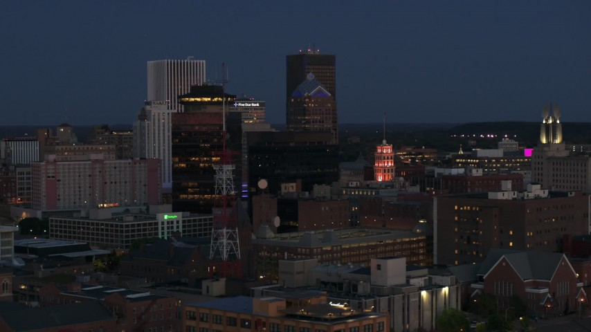 5.7K stock footage aerial video of flying by the First Federal Plaza, The Powers Building at twilight, Downtown Rochester, New York Aerial Stock Footage | DX0002_210_020