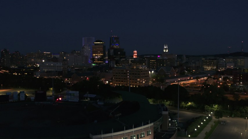 5.7K stock footage aerial video reverse view of office buildings, reveal stadium at night, Downtown Rochester, New York Aerial Stock Footage | DX0002_210_026