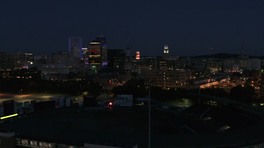 5.7K stock footage aerial video of office buildings seen from baseball stadium at night, Downtown Rochester, New York Aerial Stock Footage | DX0002_210_027