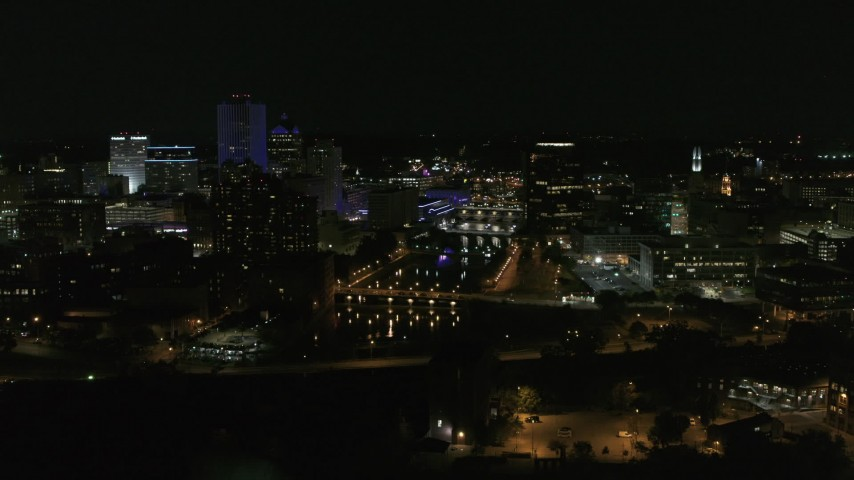5.7K stock footage aerial video of the Genesee River and skyline seen during ascent at night, Downtown Rochester, New York Aerial Stock Footage | DX0002_210_038