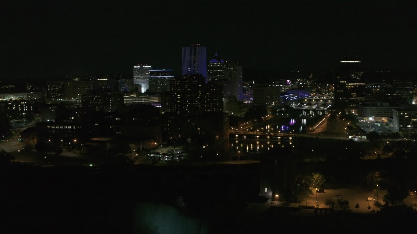 5.7K stock footage aerial video descend and orbit of city's skyline by the Genesee River at night, Downtown Rochester, New York Aerial Stock Footage | DX0002_210_047
