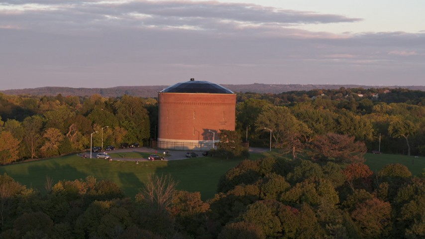 5.7K stock footage aerial video of the Stewart Stand Pipe at Thornden Park while descending, Syracuse at sunset, New York Aerial Stock Footage | DX0002_214_031