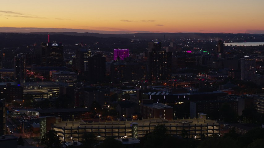 5.7K stock footage aerial video of office and city buildings lit up for the evening in Downtown Syracuse at sunset, New York Aerial Stock Footage | DX0002_214_036
