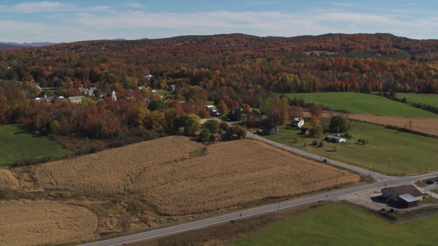 5.7K stock footage aerial video of flying away from a small town beside a forest in autumn, Orwell, Vermont Aerial Stock Footage | DX0002_217_010