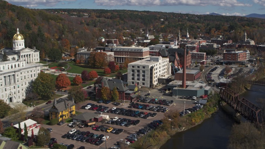 5.7K stock footage aerial video ascend over river to reveal government offices and smoke stack by the river, Montpelier, Vermont Aerial Stock Footage | DX0002_218_019