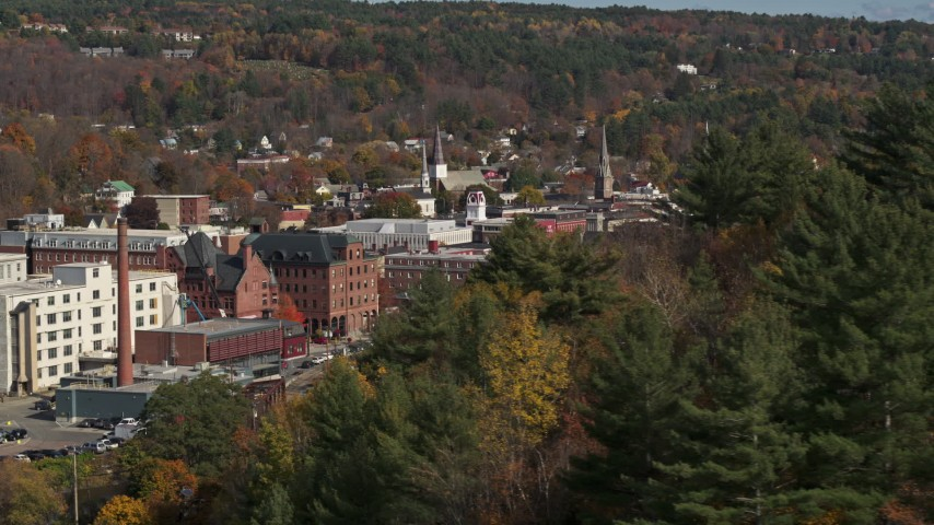 5.7K stock footage aerial video of flying by autumn trees with smoke stack in the background, Montpelier, Vermont Aerial Stock Footage | DX0002_218_033
