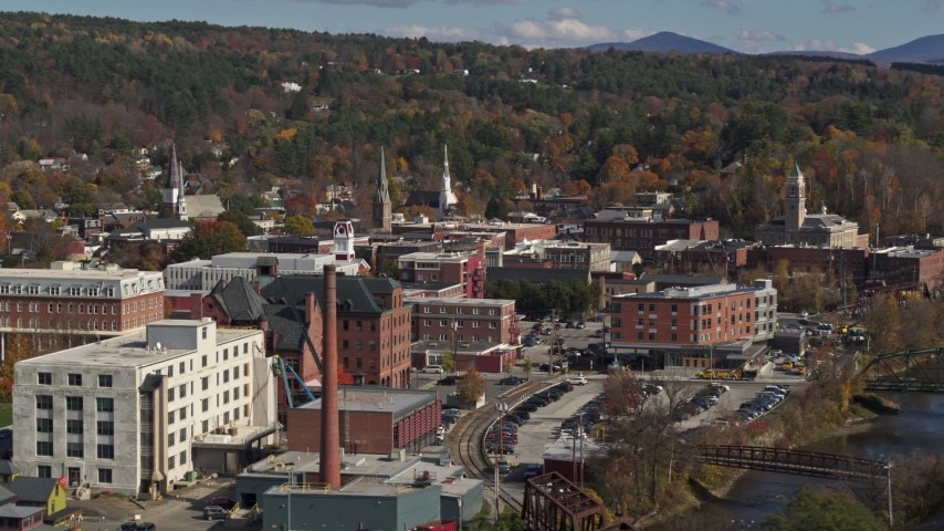 5.7K stock footage aerial video of flying by trees to reveal office buildings by a smoke stack, Montpelier, Vermont Aerial Stock Footage | DX0002_218_034