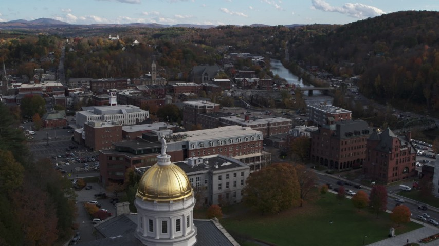5.7K stock footage aerial video of flying over the Vermont State House dome toward brick buildings in Montpelier Aerial Stock Footage | DX0002_219_007