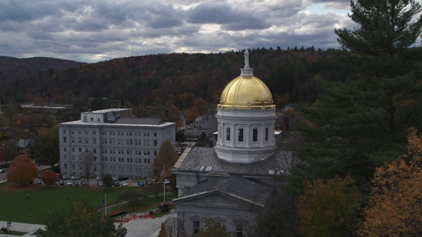 5.7K stock footage aerial video focus on the capitol while flying behind trees, Montpelier, Vermont Aerial Stock Footage | DX0002_219_017
