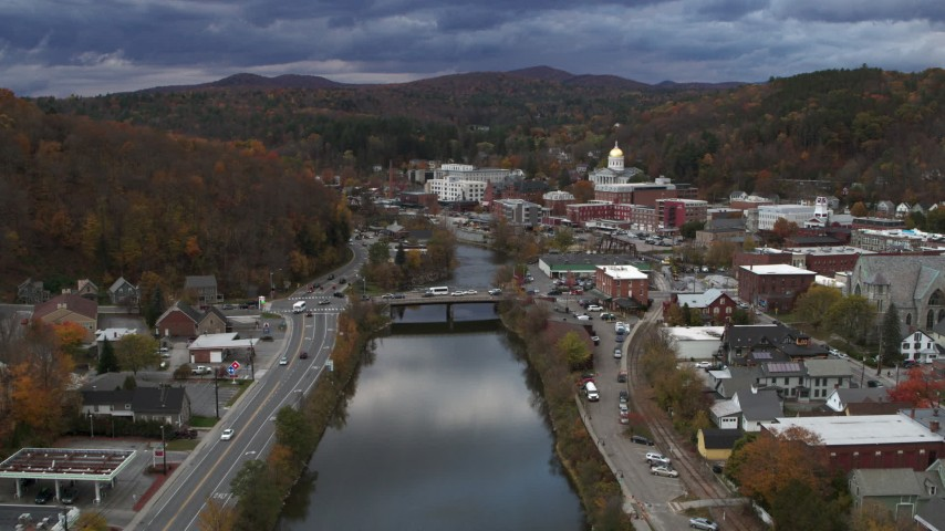 5.7K stock footage aerial video reverse view of a bridge spanning the Winooski River at sunset, Montpelier, Vermont Aerial Stock Footage | DX0002_220_002
