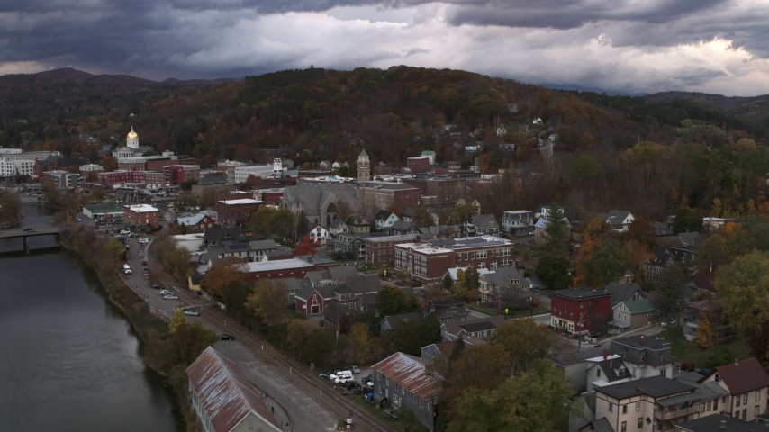 5.7K stock footage aerial video of the city hall clock tower rising above brick buildings at sunset, Montpelier, Vermont Aerial Stock Footage | DX0002_220_015