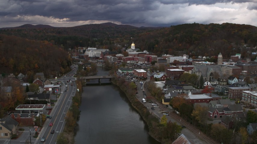 5.7K stock footage aerial video of flying by a bridge on the river with a view of the state capitol at sunset, Montpelier, Vermont Aerial Stock Footage | DX0002_220_017