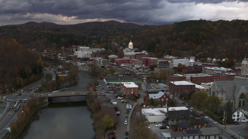 5.7K stock footage aerial video of flying over a bridge on the river with a view of the state capitol at sunset, Montpelier, Vermont Aerial Stock Footage | DX0002_220_018