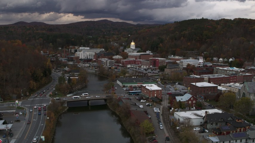 5.7K stock footage aerial video reverse view of the state capitol at sunset while flying away from a bridge over the river, Montpelier, Vermont Aerial Stock Footage | DX0002_220_023