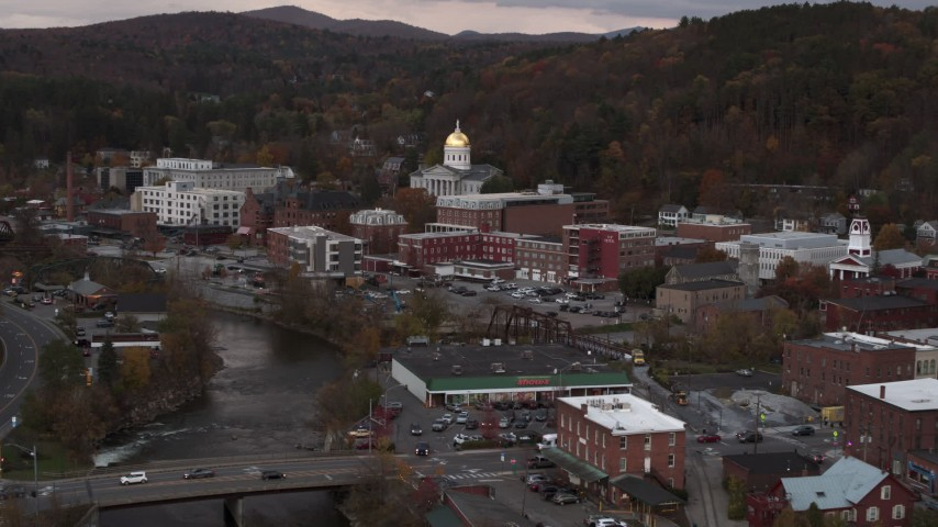 5.7K stock footage aerial video ascend and fly away from capitol dome at sunset seen from the river, Montpelier, Vermont Aerial Stock Footage | DX0002_220_025