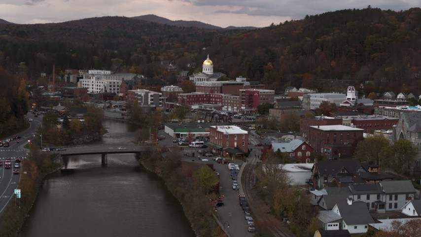 5.7K stock footage aerial video descend by the river with a view of the capitol dome at sunset, Montpelier, Vermont Aerial Stock Footage | DX0002_220_026