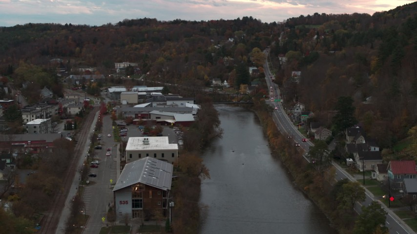 5.7K stock footage aerial video of flying by and away from the river and Berlin Street at sunset, Montpelier, Vermont Aerial Stock Footage | DX0002_220_035