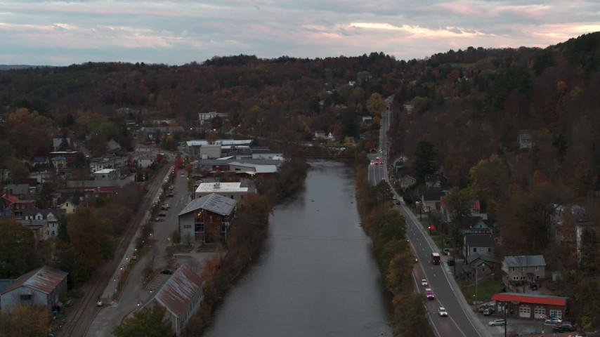 5.7K stock footage aerial video of a stationary view of the river and Berlin Street at sunset, Montpelier, Vermont Aerial Stock Footage | DX0002_220_036