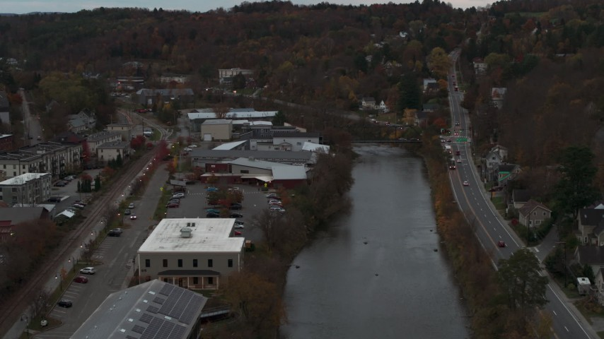 5.7K stock footage aerial video of flying away from a grocery store by the river at sunset, Montpelier, Vermont Aerial Stock Footage | DX0002_220_038