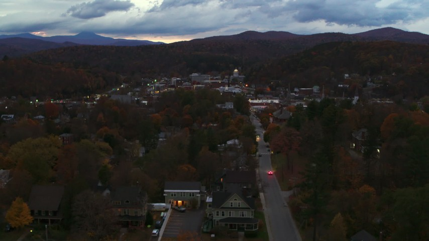 5.7K stock footage aerial video of the downtown area of the city seen from homes and fall trees at twilight, Montpelier, Vermont Aerial Stock Footage | DX0002_220_052