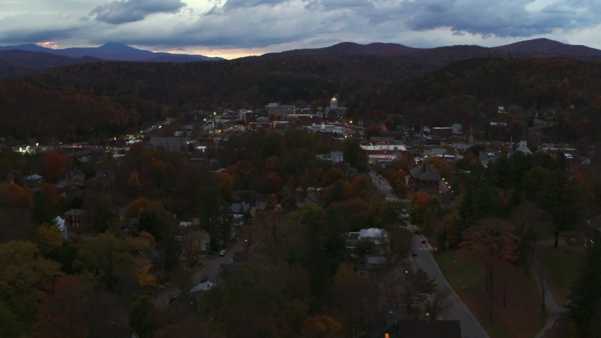 5.7K stock footage aerial video of a view of the downtown area of the city seen from homes and fall trees at twilight, Montpelier, Vermont Aerial Stock Footage | DX0002_220_053