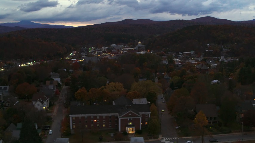 5.7K stock footage aerial video of flying by the downtown area of the city seen from homes and fall trees at twilight, Montpelier, Vermont Aerial Stock Footage | DX0002_220_054