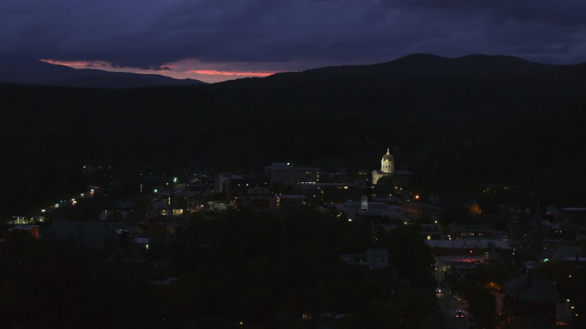 5.7K stock footage aerial video of a view of the capitol dome lit up at twilight and downtown buildings, Montpelier, Vermont Aerial Stock Footage | DX0002_220_060