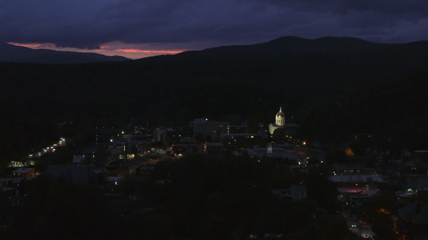 5.7K stock footage aerial video of flying by the capitol dome lit up at twilight and downtown buildings, Montpelier, Vermont Aerial Stock Footage | DX0002_220_061