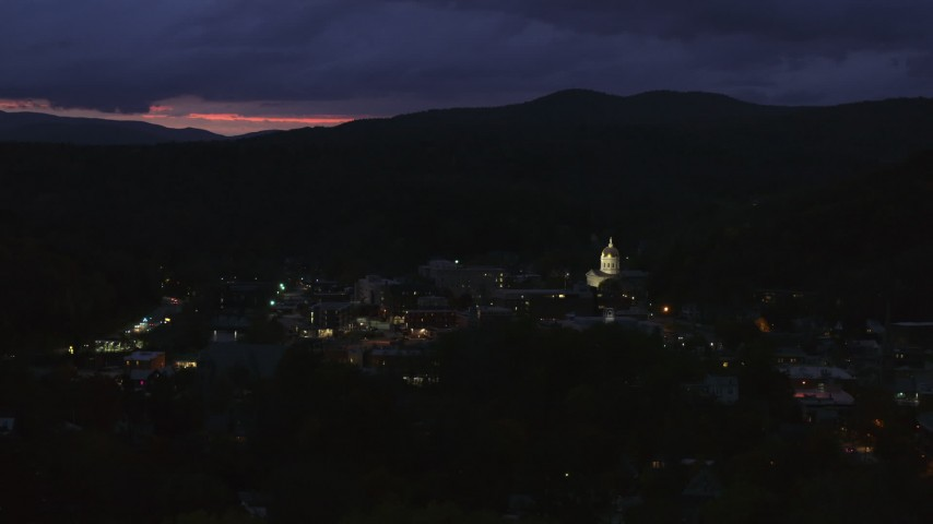 5.7K stock footage aerial video of flying by downtown buildings around the capitol dome lit up at twilight, Montpelier, Vermont Aerial Stock Footage | DX0002_220_062
