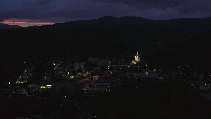 5.7K stock footage aerial video of passing by city buildings around the capitol dome lit up at twilight, Montpelier, Vermont Aerial Stock Footage | DX0002_220_063