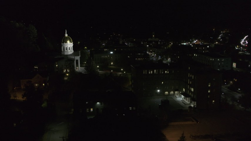 5.7K stock footage aerial video of the Vermont State Capitol behind a dark building at night, Montpelier, Vermont Aerial Stock Footage | DX0002_221_017