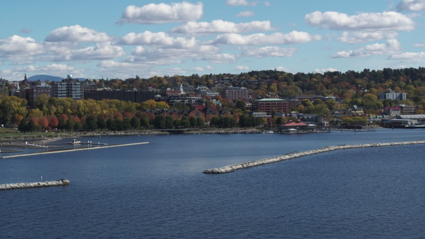 5.7K stock footage aerial video of buildings in downtown seen from breakwaters in the lake, Burlington, Vermont Aerial Stock Footage | DX0002_222_043