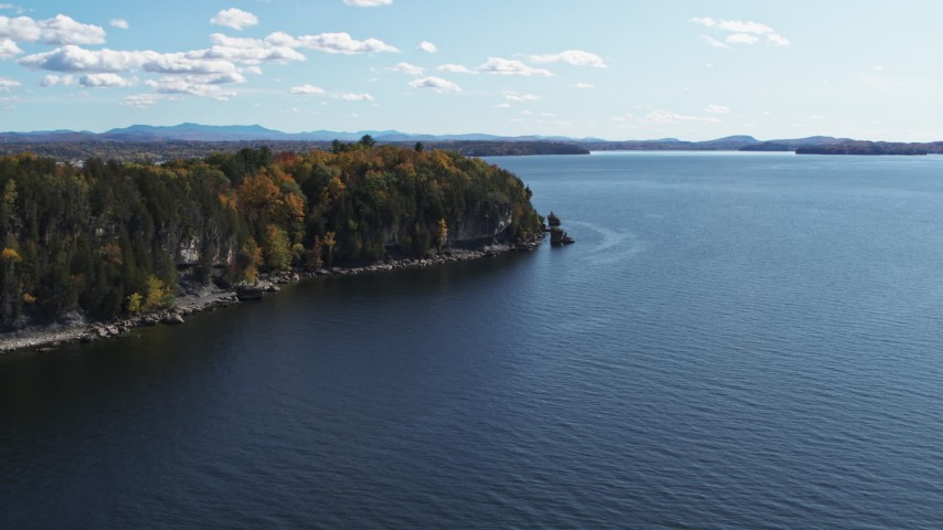 5.7K stock footage aerial video ascend away from forest on the tip of Lone Rock Point by Lake Champlain, Burlington, Vermont Aerial Stock Footage | DX0002_223_024