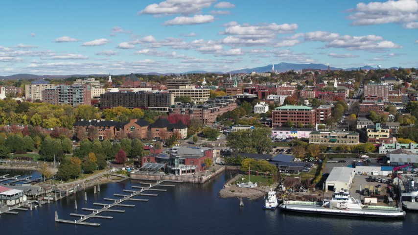 5.7K stock footage aerial video of downtown buildings seen while passing a marina, Burlington, Vermont Aerial Stock Footage | DX0002_224_010