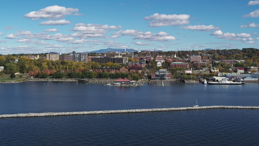 5.7K stock footage aerial video a view of downtown buildings seen while descending by breakwaters, Burlington, Vermont Aerial Stock Footage | DX0002_224_014