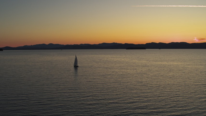 5.7K stock footage aerial video of flying away from a sailboat on Lake Champlain at twilight, Burlington, Vermont Aerial Stock Footage | DX0002_225_036
